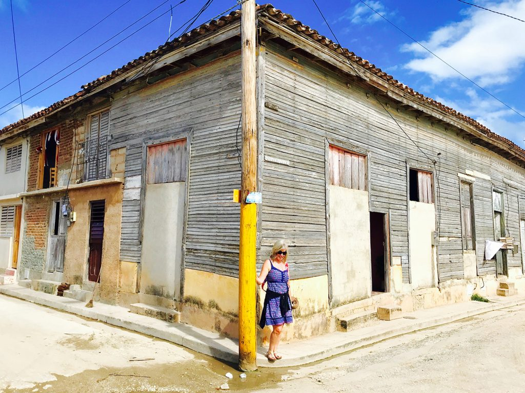 A woman standing in front of an old building.