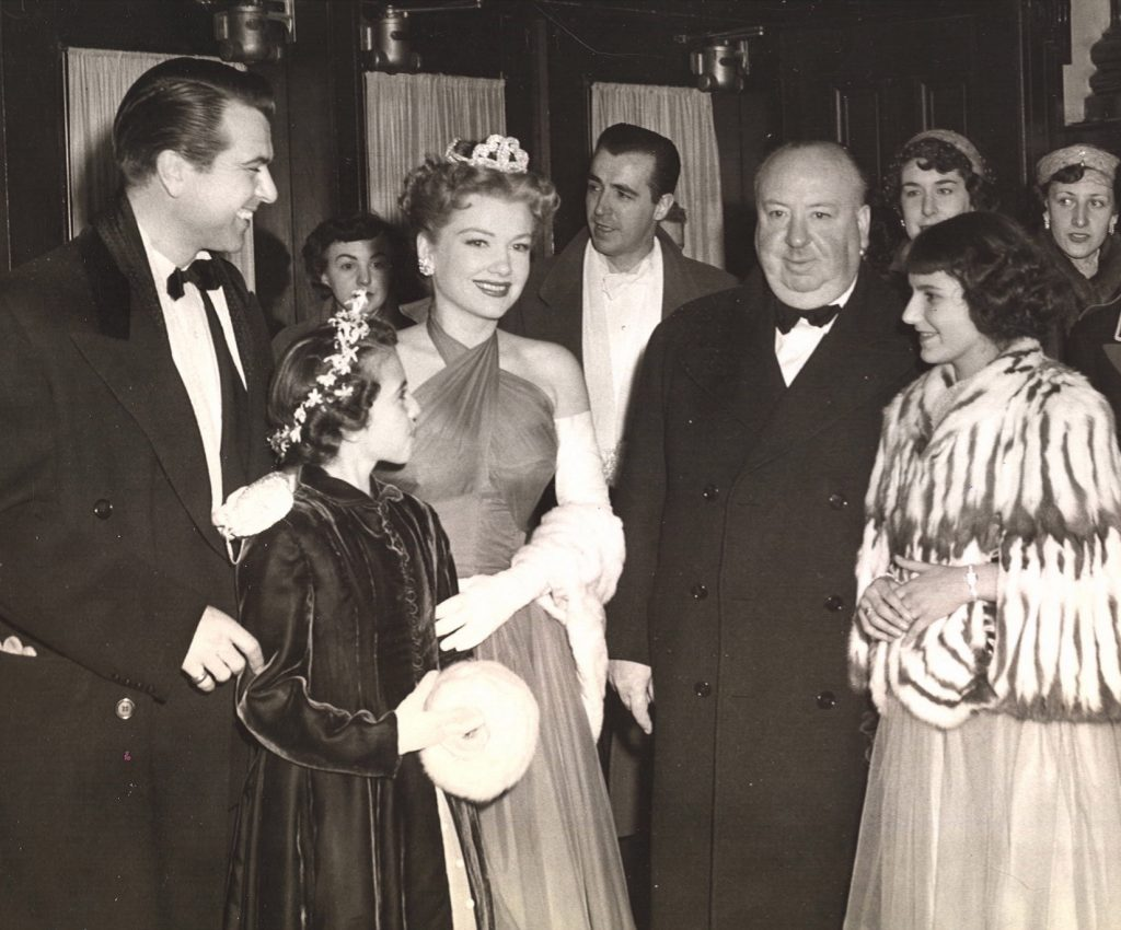 Director Alfred Hitchcock arrives at Quebec's Capitol Theatre for the premiere of his film I Confess, which was filmed on location in the city. Also pictured, left to right, are Roger Dann, Renée Hudon, Anne Baxter, and Carmen Gingras.