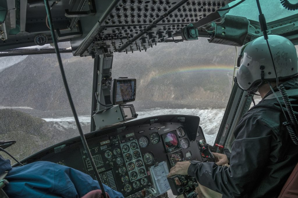 A helicopter flies though a snowshower in theh Cariboos with a rainbow to the right.