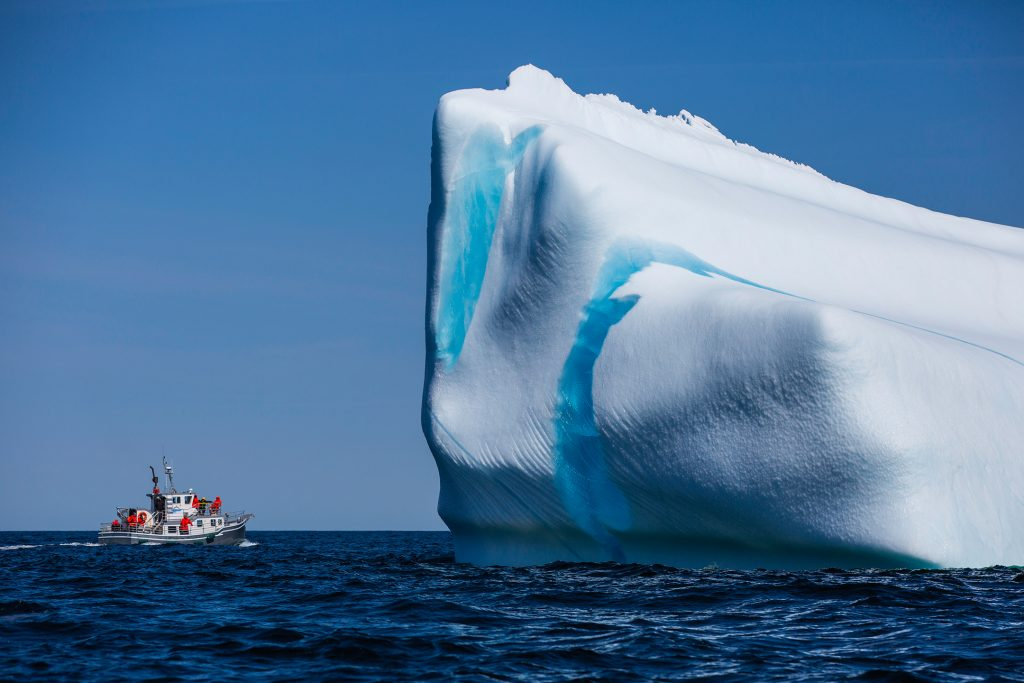A fishing boat is dwarfed by a large blue and white iceberg