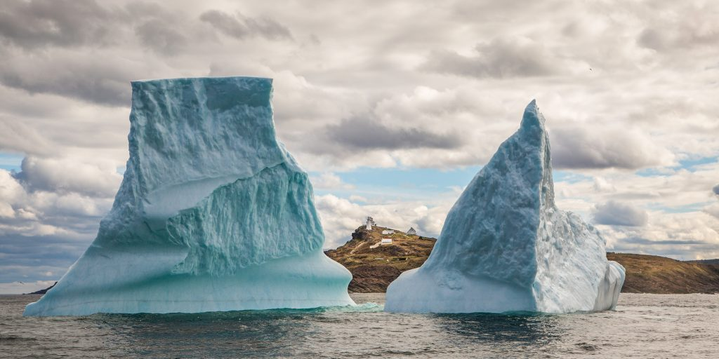 A small fishing village is seen between two halves of a large iceberg at Cape Spear, Newfoundland