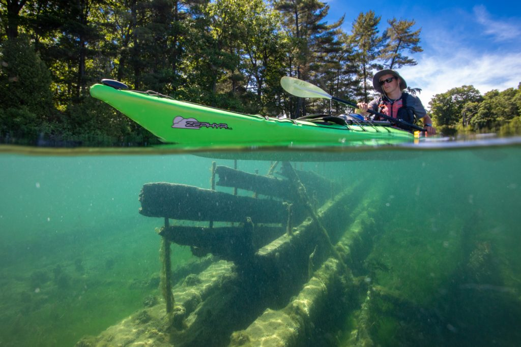 A kayaker floats above a submerged shipwreck