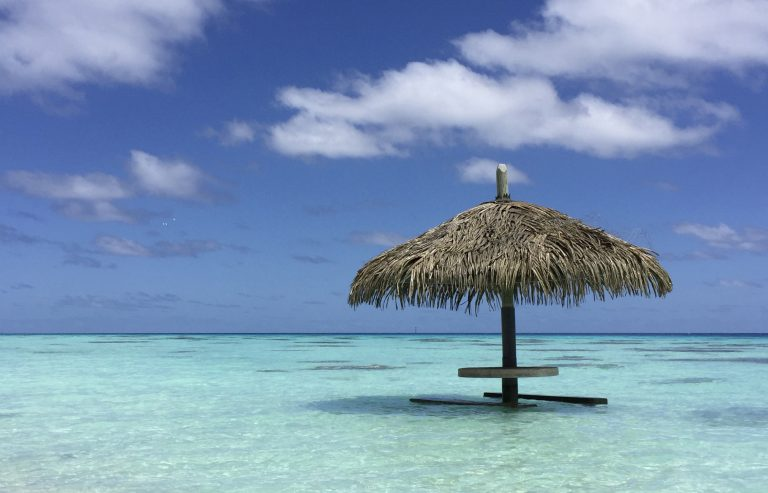 thatched table in blue water, beach, tahiti, tropical