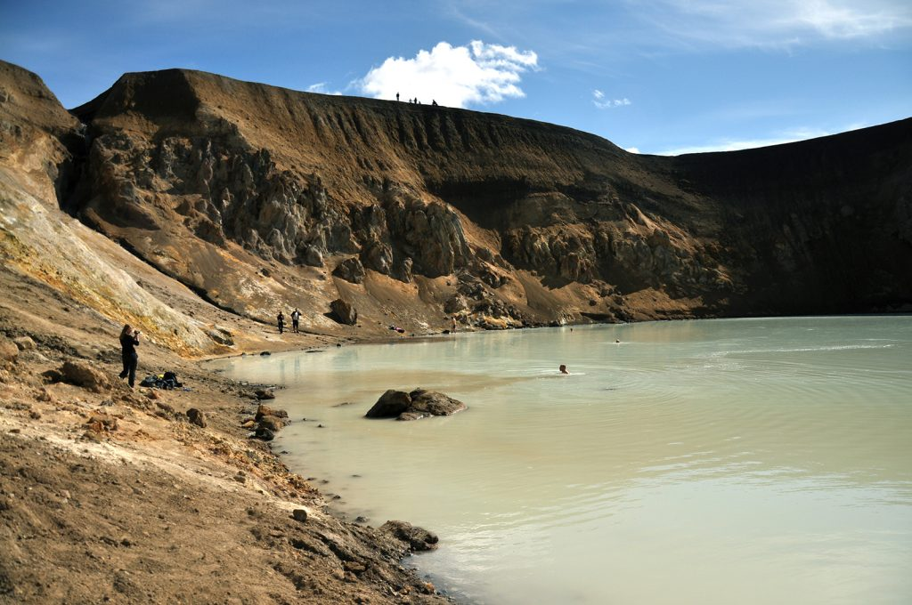 People bathe in a milky-green-coloured volcanic crater lake