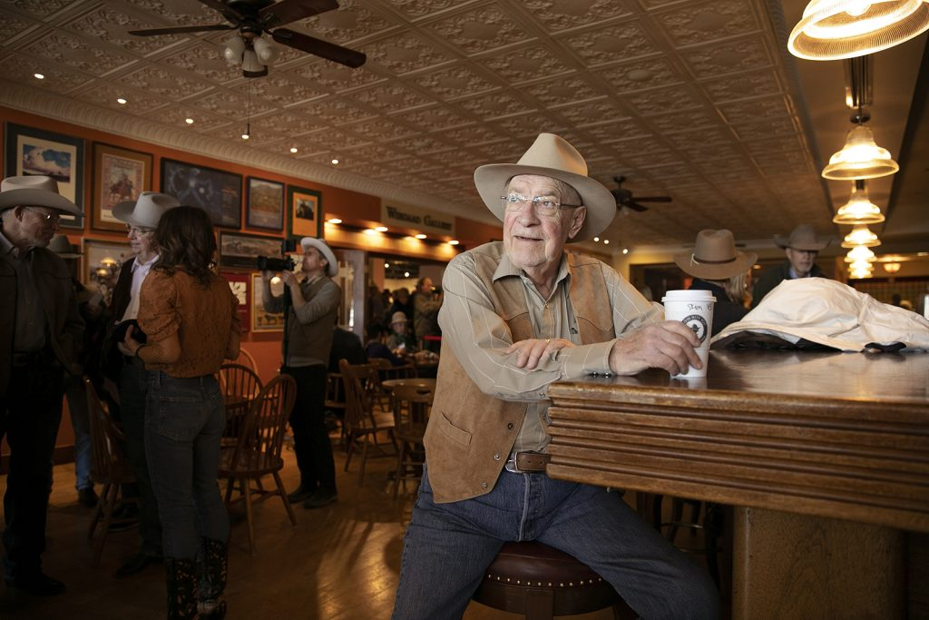 An elderly man in a cowboy hat drinks coffee while sitting at a bar