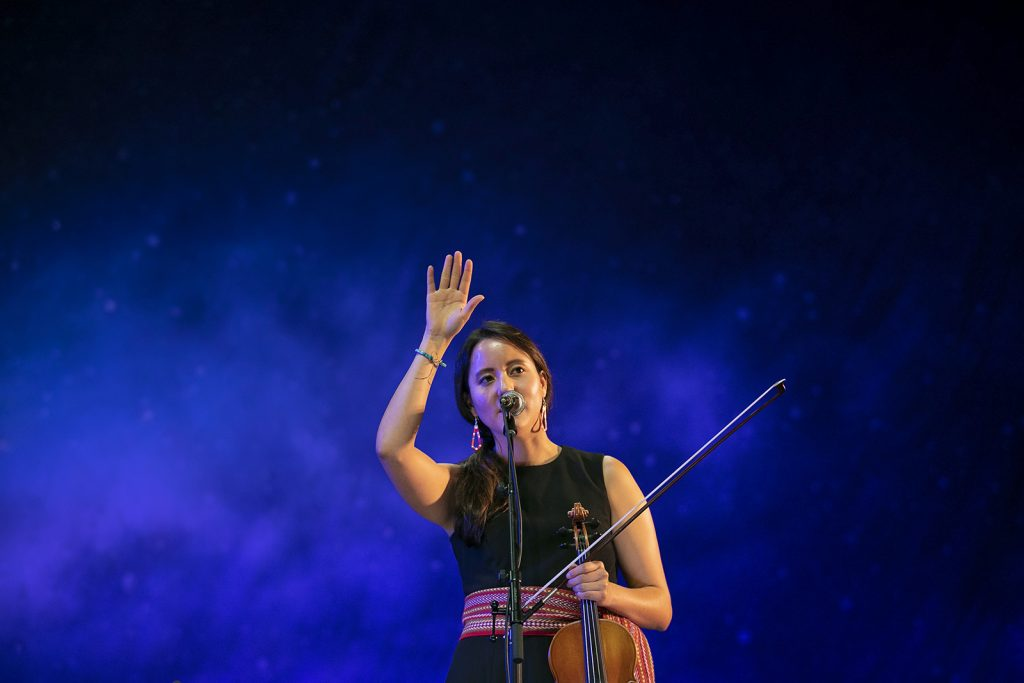 A Métis woman wearing a black dress with a ceinteur fléchée and holding a fiddle waves to the audience