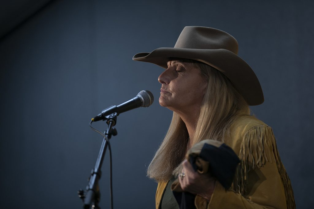 A blonde woman wearing a cowboy hat closes her eyes as she speaks into a microphone