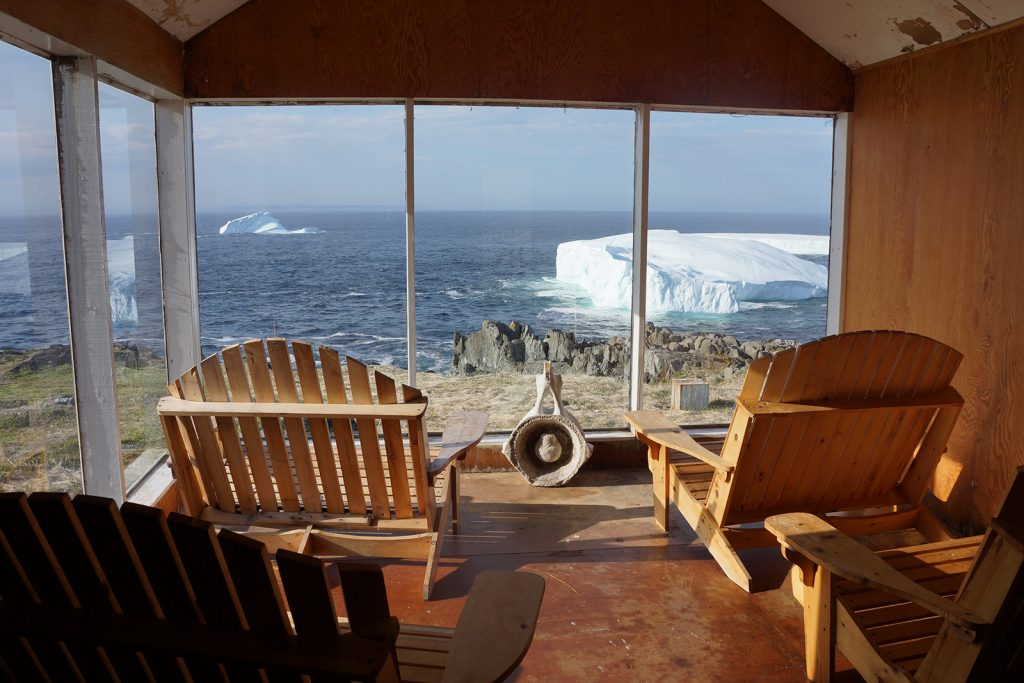 Two wooden muskoka chairs look out over a view of ocean and icebergs
