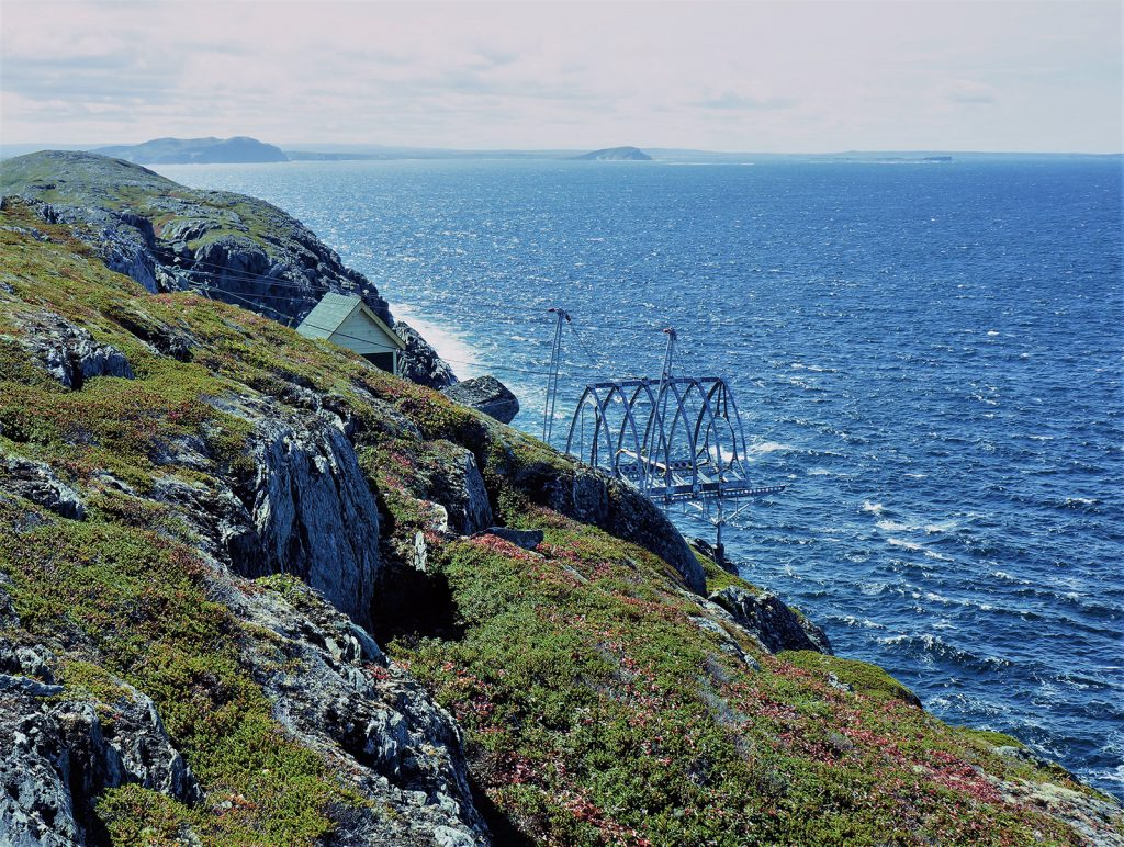 A metal frame anchored in a cliff juts out over a blue ocean. This is a whale-watching pod under construction.