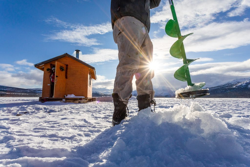 A man uses an auger to drill a hole for ice fishing as the sun sets