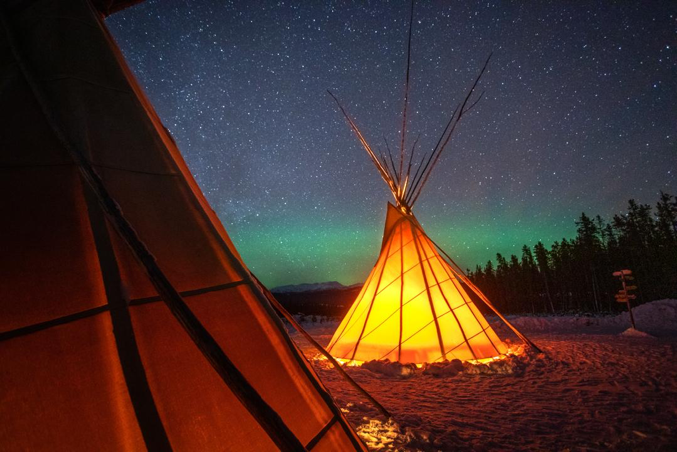 A teepee, lit from within, stands out against a starry night sky with aurora borealis visible on the horizon
