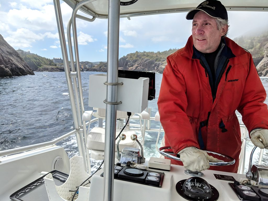 A man in a red raincoat steers a fishing boat through Quidi Vidi Harbour