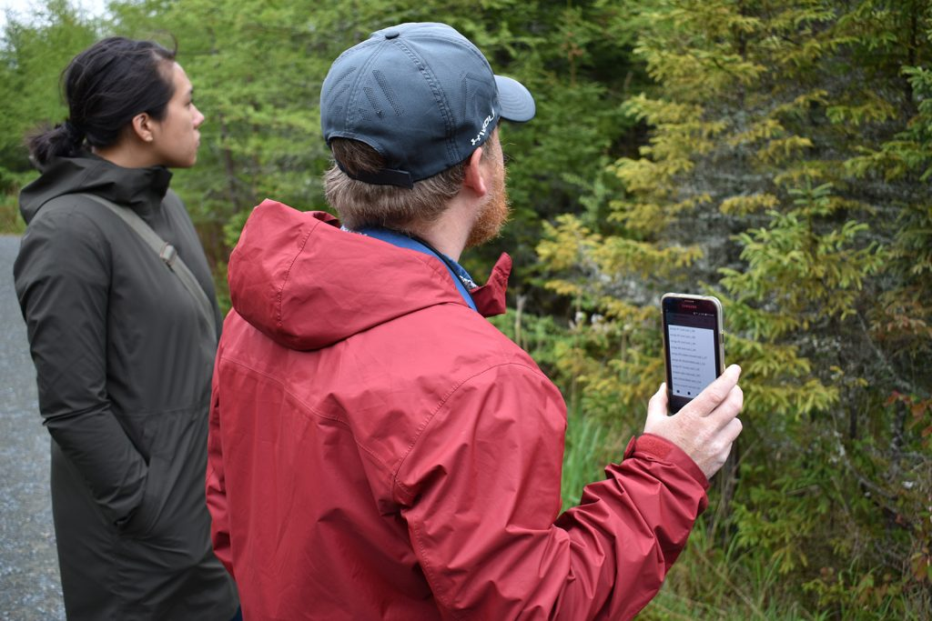 A man in a red rain jacket holds up a phone in front of some trees, playing a bird call