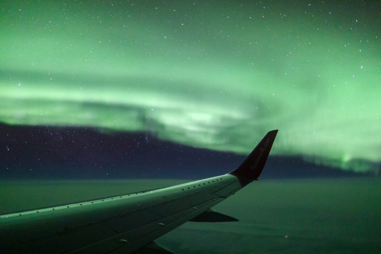 Airplane wingtip against night sky surrounded by stars and bright green aurora borealis