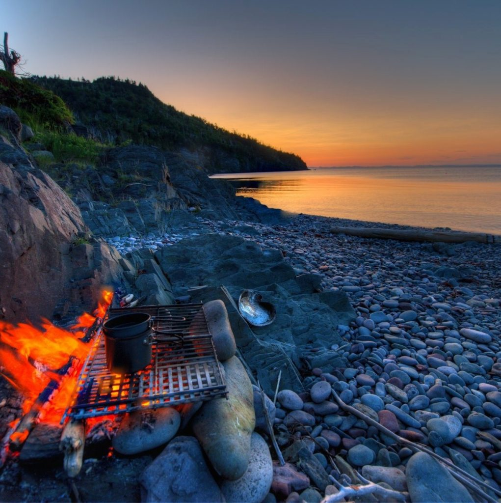 Small campfire on rocky beach at sunset