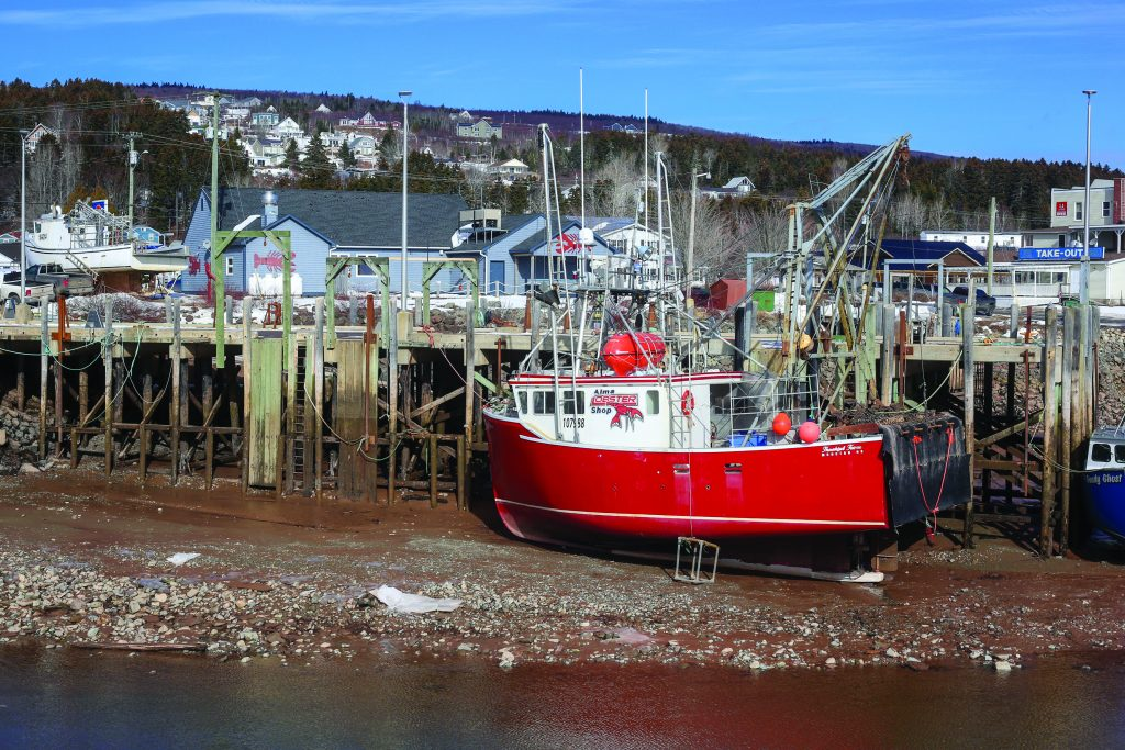 A fishing boat sits on the ocean floor by a dock in the Bay of Fundy