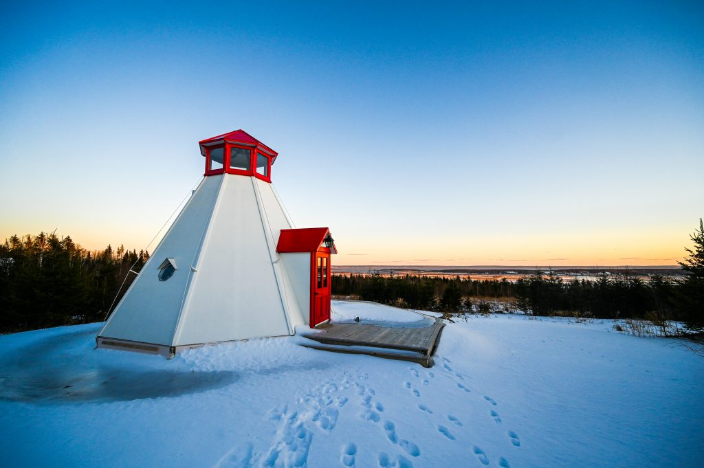 A lighthouse at sunset on a snow covered day