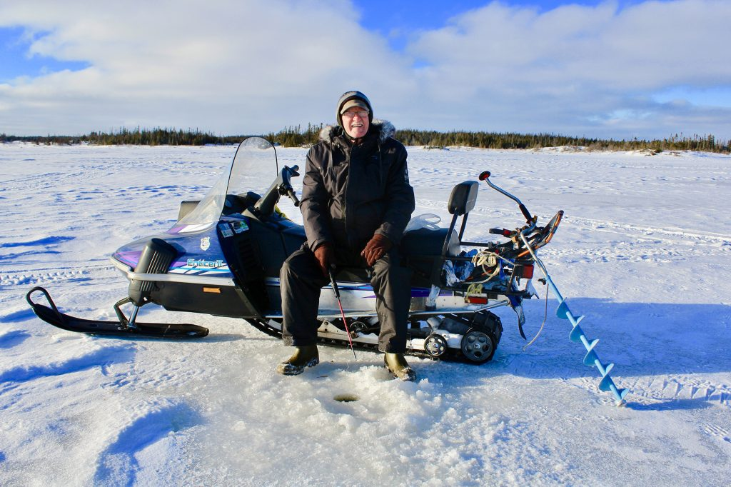 Martin Foley ice fishes from a snowmobile on Fogo Island, N.L.