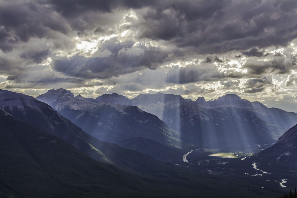 The sun shines through the clouds over mountains