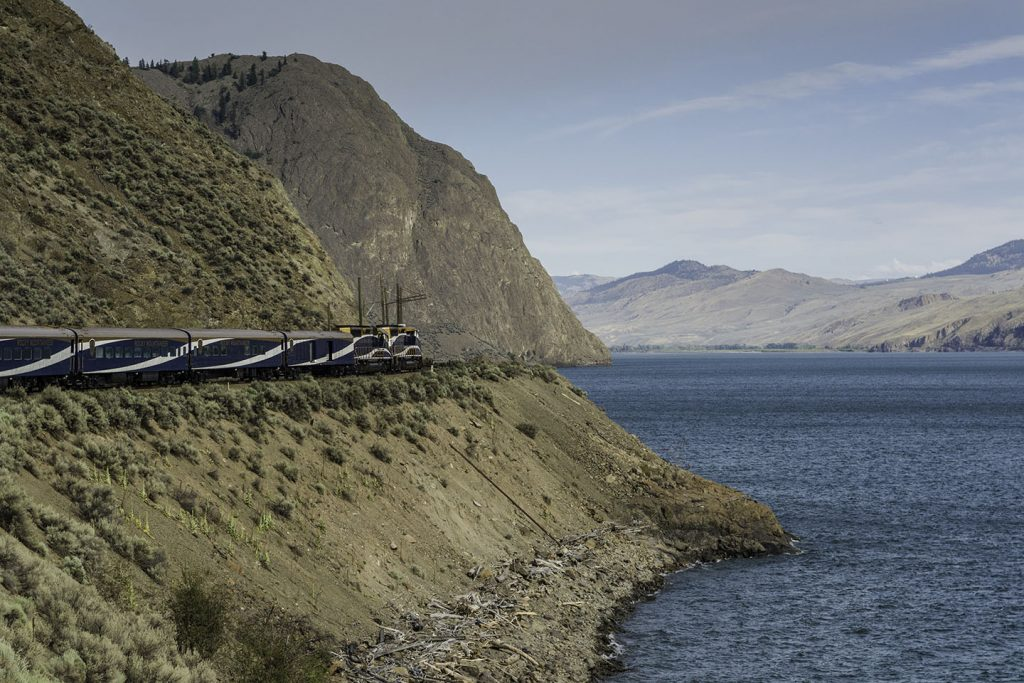 A cliff overlooking a river with a train passing by