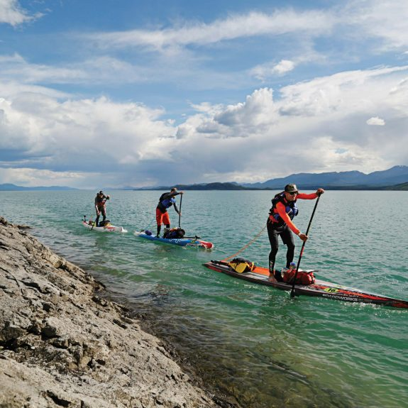Three people paddle board through the water with mountains in the background.
