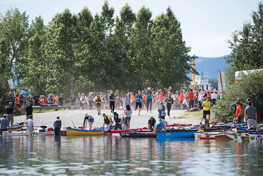 People stand in canoes by the edge of the water, while others stand on the beach