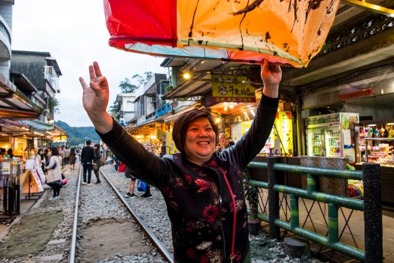 A woman smiles as she launches a paper lantern
