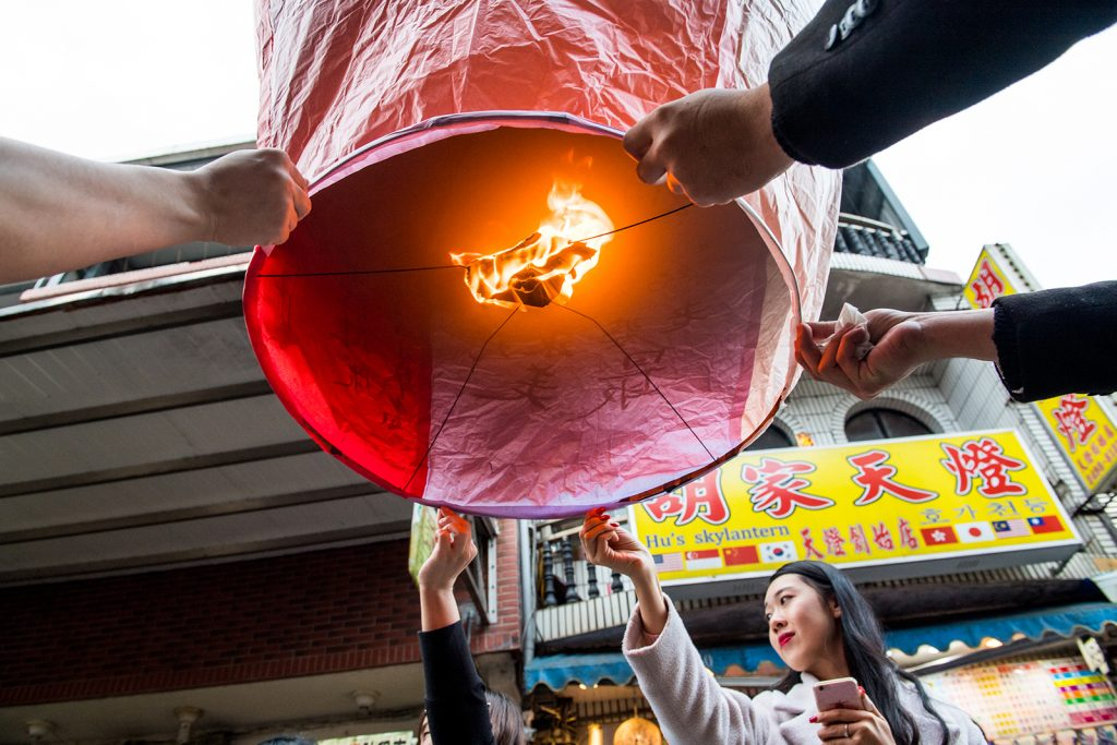 A woman holds a paper lantern with others helping.