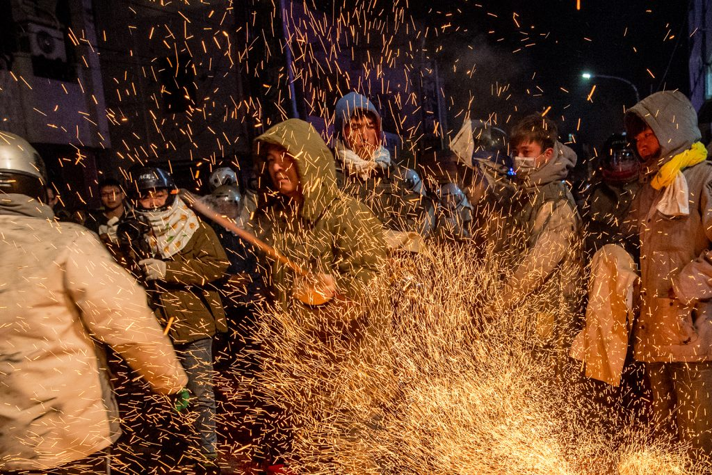 A crowd looks on as fireworks spray in front of them.