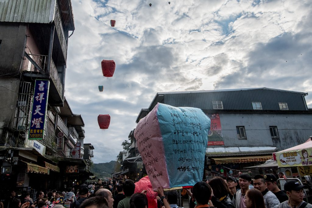 Paper lanterns are launched into the sky by a crowd.
