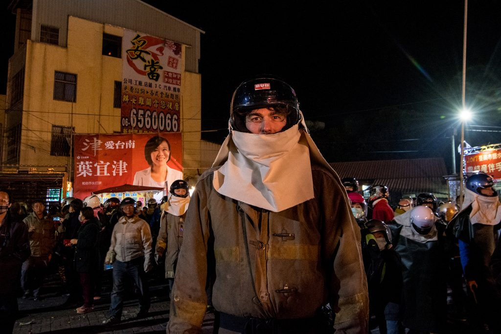 A man in protective gear stands in front of a crowd