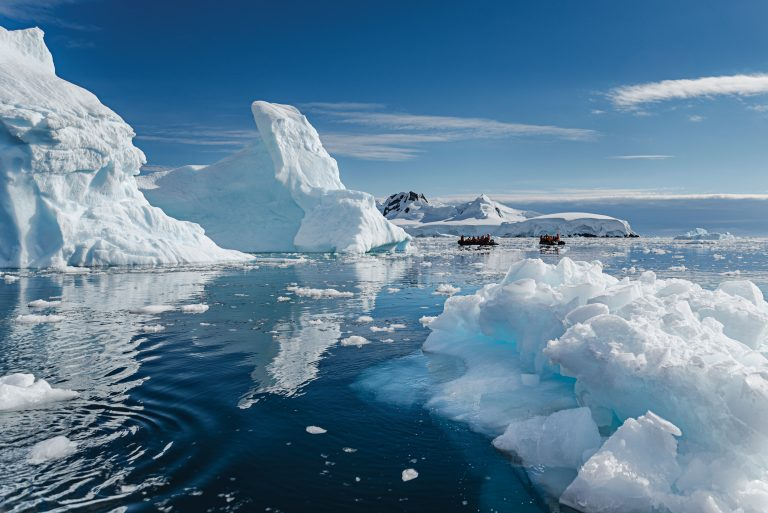 Two boats float past icebergs in Antarctic waters