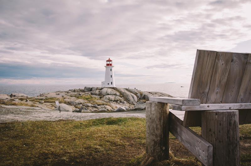 A lighthouse sits on a rocky hill, with the edge of a wooden bench in the foreground