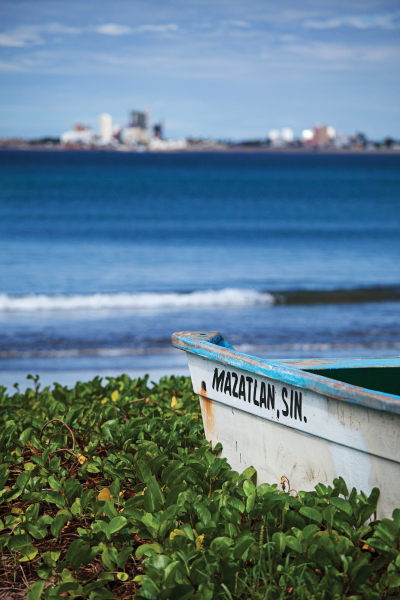 A fishing boat on a Mexican shore with a city on the far side of the water in the background.