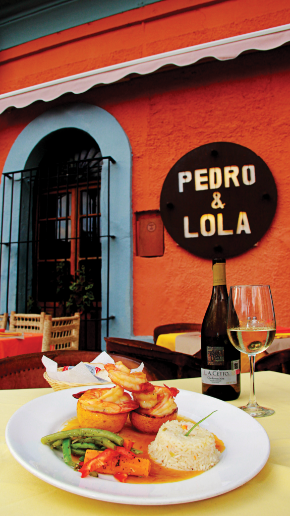 A table is set outside a colourful restaurant called Pedro & Lola