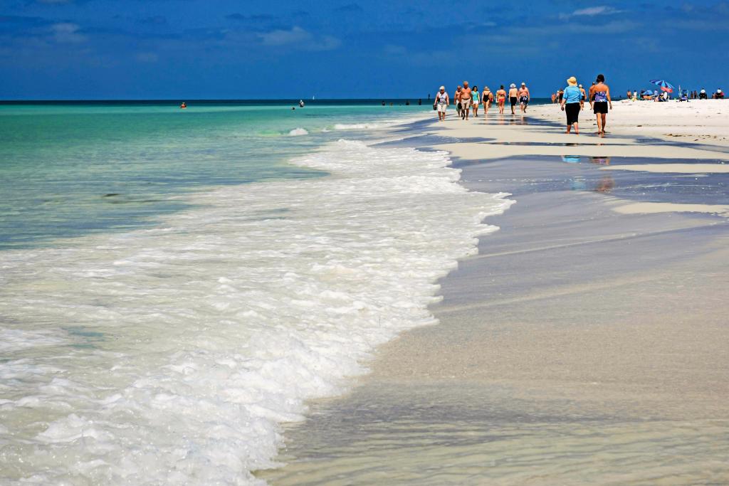 Beachgoers walk along white sands next to turquoise ocean