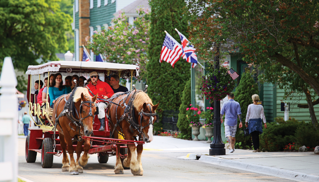 Tourists sit in a carriage pulled by two horses along a picturesque street.