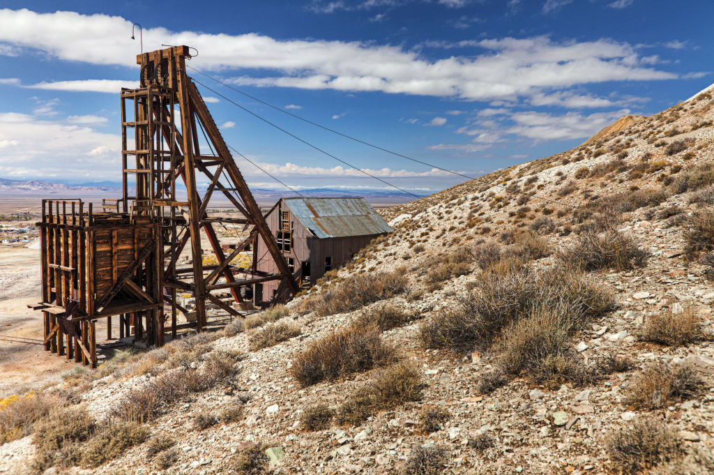 An old mine's head frame sits in a desert landscape.
