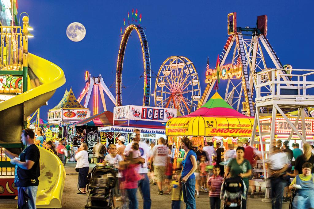 Crowds enjoy a brightly lit fairground at night