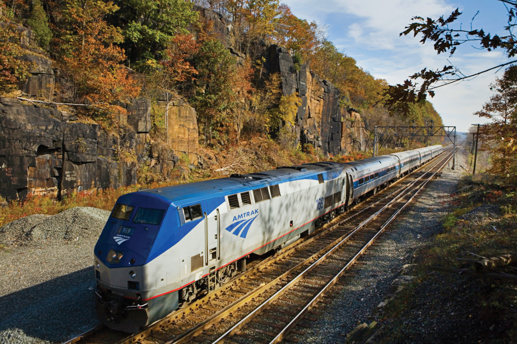 Amtrak train passes through a sunlit mountainous region.