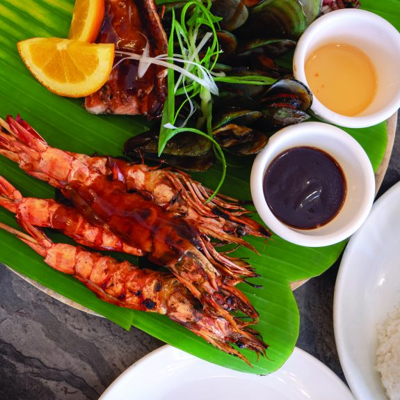 Grilled seafood platter with barbecue sauce on banana leaf