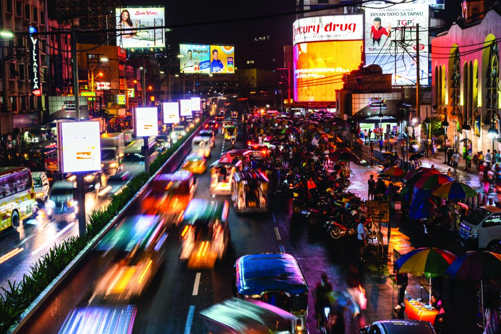 wide angle view showing busy street cars and market vendors on the street and people buying at night in the Qiapo area of Manila with people on the background