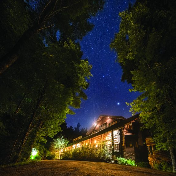 Nighttime view of a rustic, well-lit lodge.