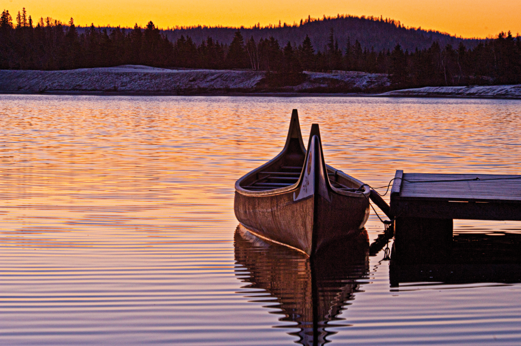 A canoe floats on a peaceful lake during sunset