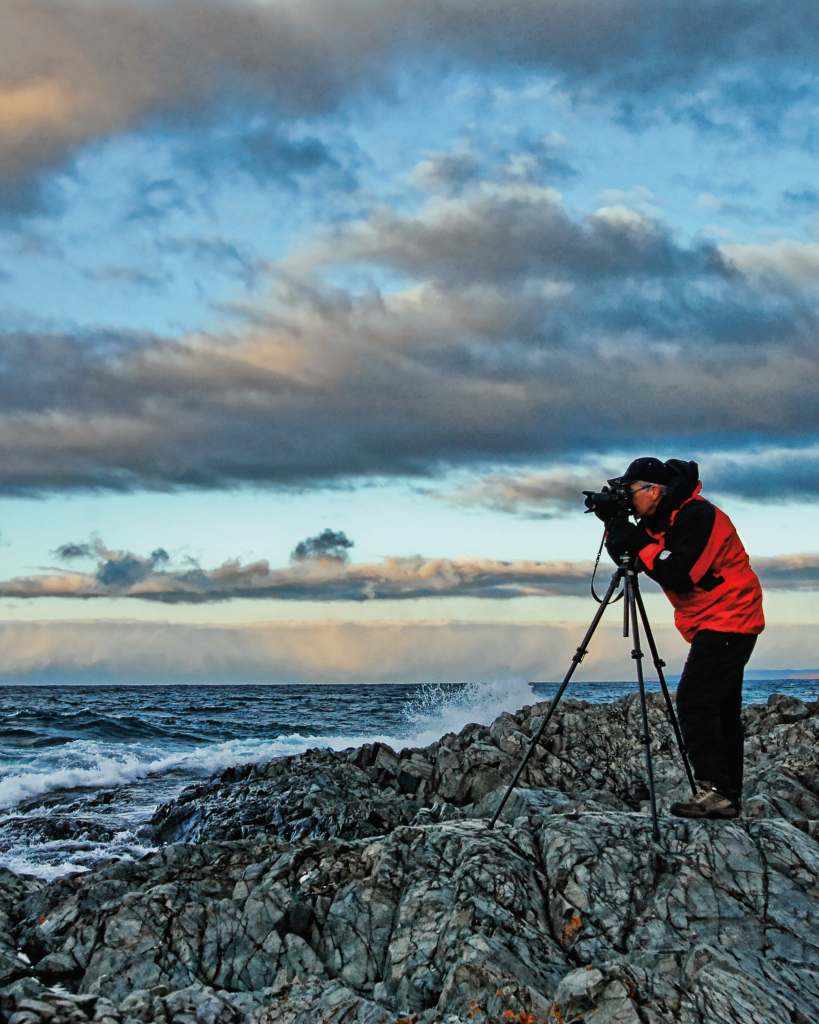 A man stands on a rocky shore with a camera on a tripod
