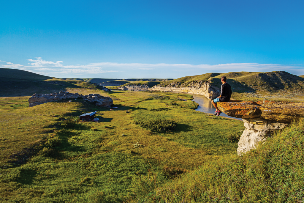 A man sits on a rocky ledge overlooking a river and expansive grasslands.