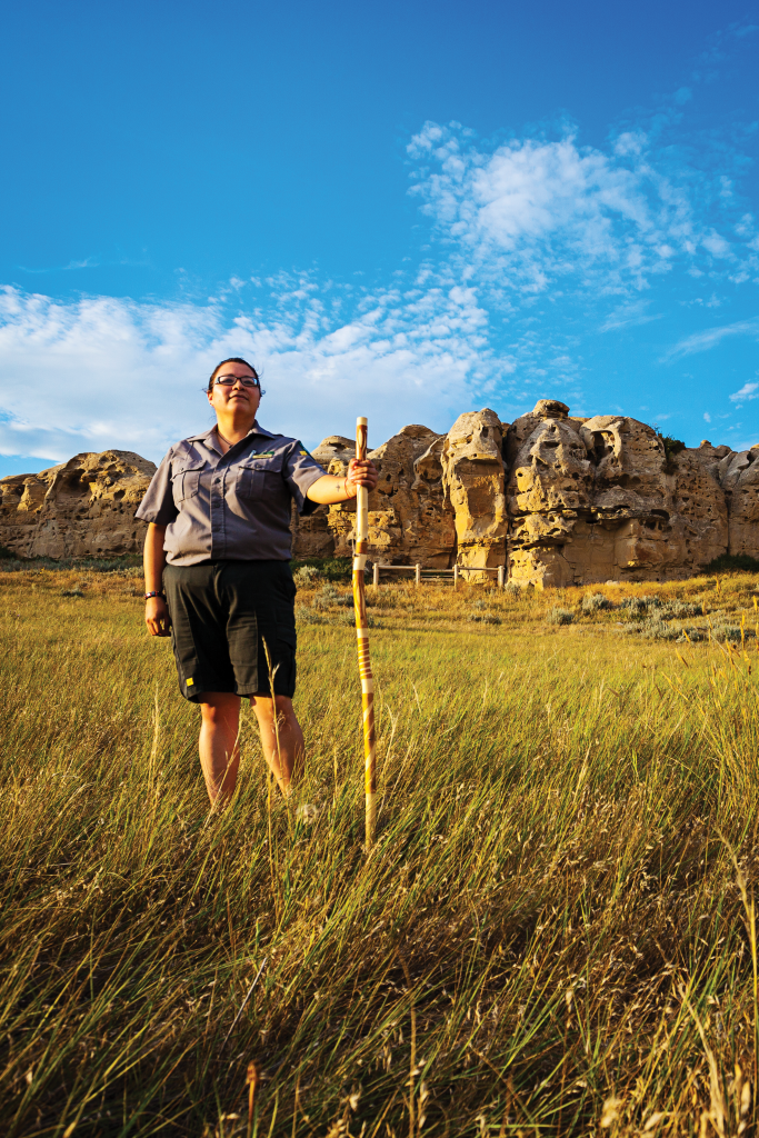 A woman stands in grasslands holding a wooden staff, cliffs in the background
