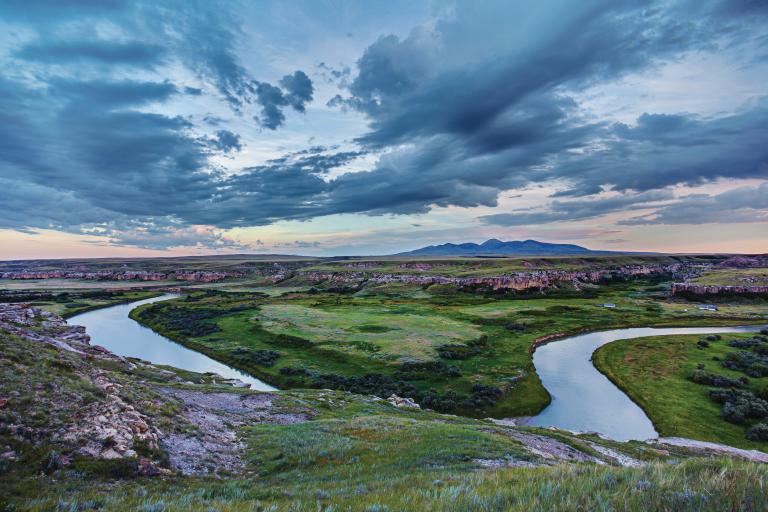 A blue river winds through a green landscape