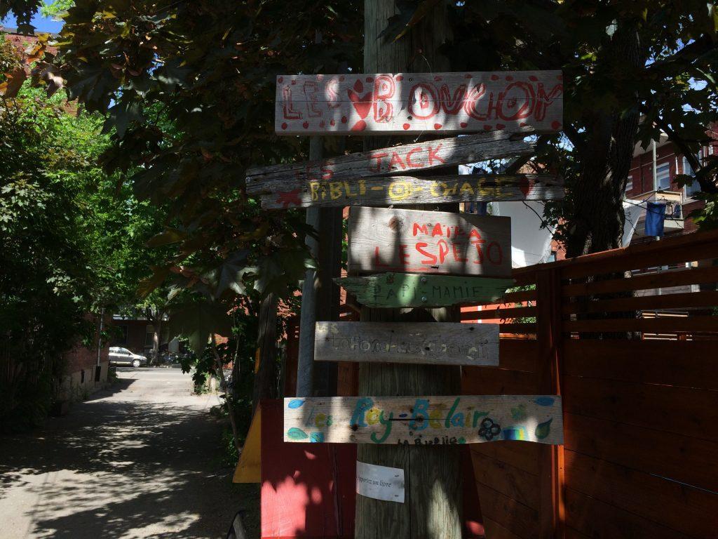 Handmade signs mark the beginning of an alleyway.
