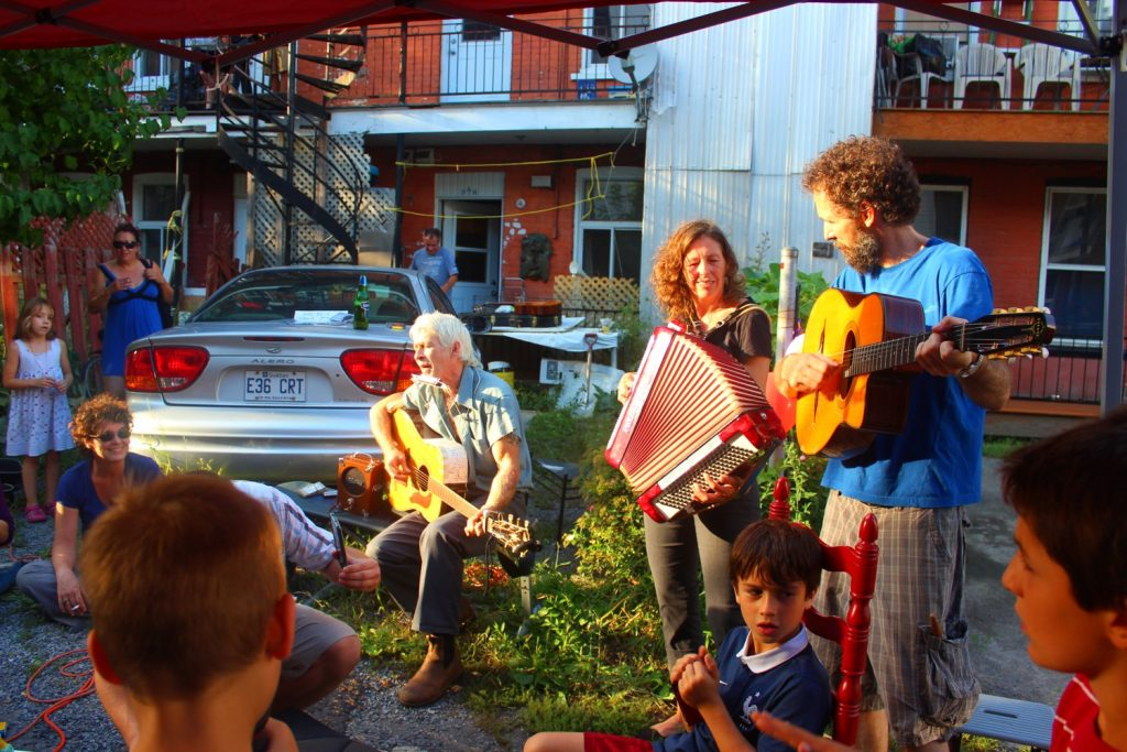 A group of musicians play perform for their neighbours in a green alley